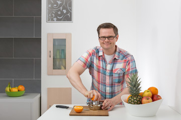 Mann presst Apfelsinen aus