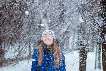 Happy laughing baby in winter forest. Young girl playing in the snow-covered snow park