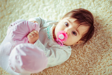 The stylish baby with dummy lies on the carpet