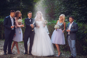 Bride and groom with happy groomsmen and bridesmaids having fun and popping champagne, luxury wedding celebration, hilarious moment. Newlyweds fun with friends.