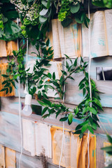 Beautiful unusual wedding decor. Rustic Style. Bench, wall of flowers, lanterns at the photo zone.
