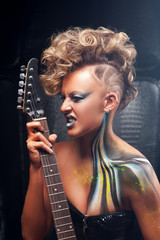 Impressed punk musician playing on guitar. Portrait of rocker girl with bright body art, emotionally performing. Subculture, expression, courage, drive, rock, lifestyle concept