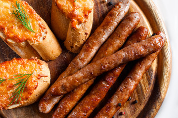 Tasty bavarian wurst with toasts flat lay. Top view on wooden catering platter served with grilled sausages and three canapes. German cuisine, beer snack, junk food concept