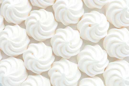 Closeup of mini meringues on white as food background.