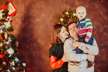 The father,mother and son stand near  Christmas Tree