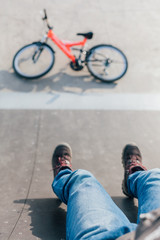Overhead of a boy's legs sitting after jumping with bike in a sk