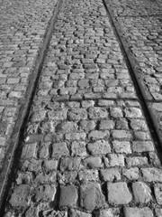 Alte Bahngleise für Güterzüge im Kopfsteinpflaster an der Hafenpromenade von Münster in Westfalen im Münsterland, aufgenommen in neorealistischem Schwarzweiß