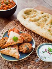 Indian snacks - pakora, samosa, onion bhaji , mint raita and garlic naan bread.