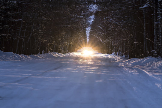 car headlights shine on winter snowy road at night in forest
