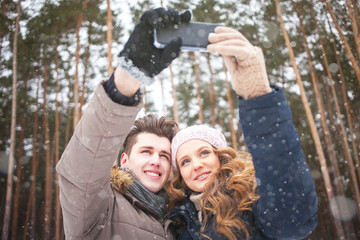 happy couple taking picture with smartphone selfie stick on over winter background