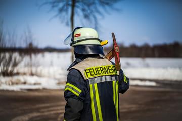 HDR - Feuerwehrmann im Einsatz draußen auf der Straße mit einer Axt