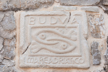 Historical sign of Budva city on stone wall, Montenegro.