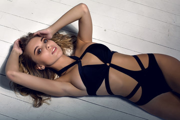 young sexual girl blonde long hair in black swimsuit is lying on white wooden floor