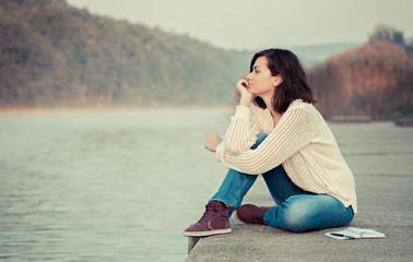 Thoughtful woman sitting by lake. Enjoying the early morning.
