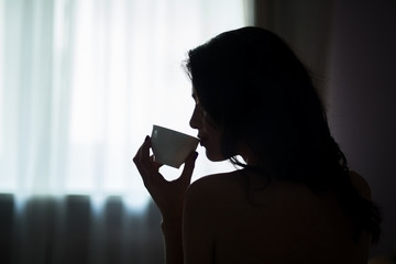 Lady holding cup in darkness. Young woman indoors. Day starts from hot beverage.