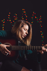 Young woman playing guitar and composing a song