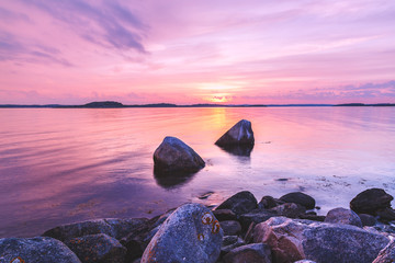Violet toning sea shore landscape with great stones at foreground. Location: Sweden, Europe.