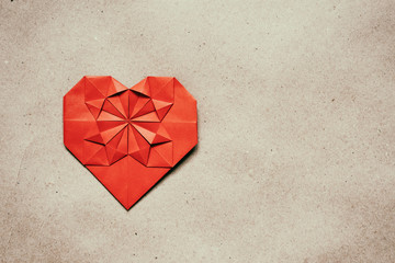 Red paper folded origami heart on natural eco brown background.