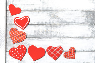 handmade toy hearts on a white wooden background. Valentine day background