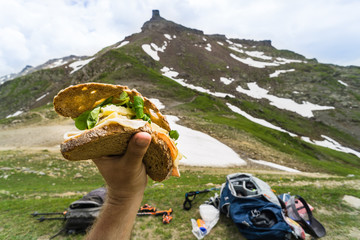 Sitting at the top of a pass along the Tour du Mont Blanc and eating a sandwich