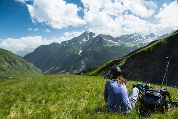 Young woman hiker rests in a meadow on a summer day in the French Alps