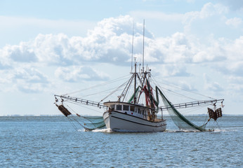 Shrimp boat in harbor heading out to sea