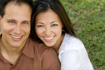 Portrait of an Asian couple laughing and hugging.