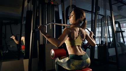 Young woman doing exercise for back on training machine