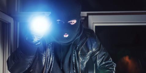 Einbrecher mit Taschenlampe am Fenster
