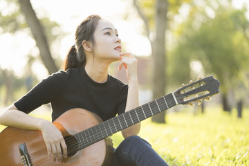 Young attractive woman playing acoustic guitar