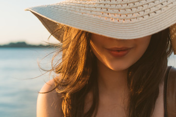 Cropped image of woman wearing hat on beach