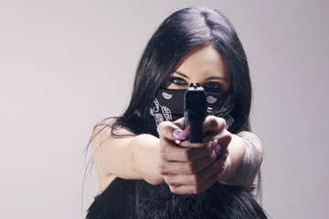 Beautiful brunette woman with a pistol pointing to camera, wearing a bandana as a thief, looking menacing. Over a grey background.