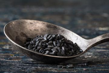 Black sesame seeds in a vintage spoon