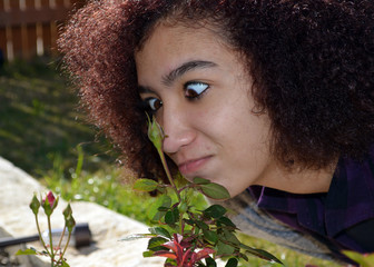 Cross Eyed KC/Close up of mixed race teen making a funny face while smelling roses