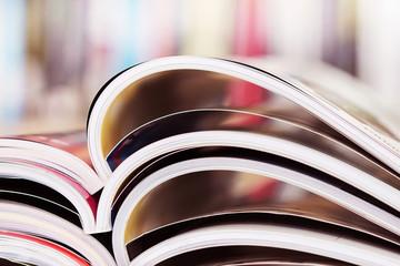 close up stacking of opened magazine with blurry bookshelf
