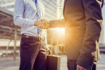 Success and Happiness Team Concept, Business man handshake at city background.