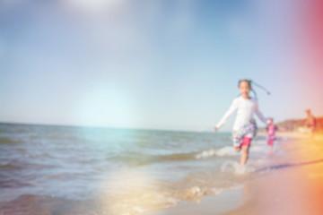 kids running at the beach, defocused image