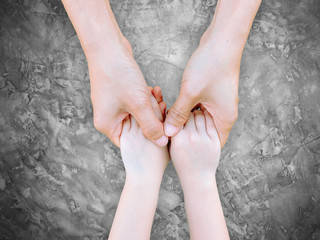 hand holding hand.Mother holding daughter's hand on cement background with clipping path.