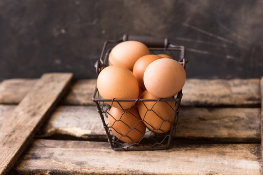 Fresh brown eggs in a wire basket on a vintage wood box, black background, Easter, decoration, rural rustic einterior, farming concept,soft colors