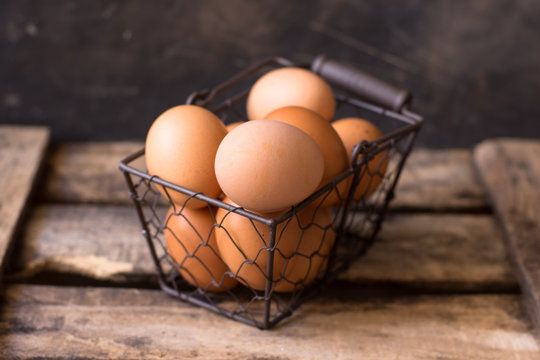 Fresh brown eggs in a wire basket on a vintage wood box, black background, Easter, decoration, rural rustic einterior, farming concept