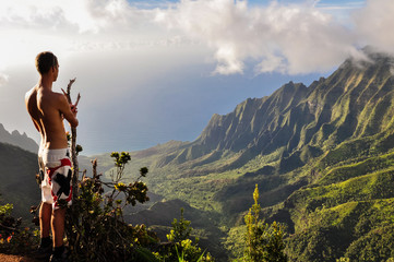 Young male topless tourist in swimming trunks overlooking Kalalau Valley at stunning Na Pali Coast on the eass side of the island of Kauai, Hawaii, USA. Tourist seen from the back. Spectacular view.