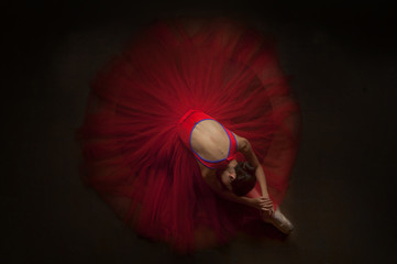 beautiful ballerina woman laying on her knee with beautiful red tutu. image