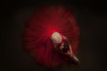 beautiful ballerina woman laying on her knee with beautiful red tutu. image