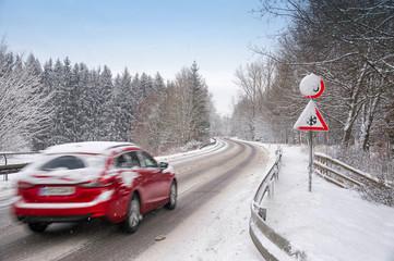 Verschneite Straße mit Auto im Winter