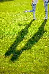 the shadow of a young couple on the grass