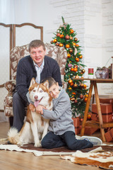 father and little boy with Husky background Christmas tree