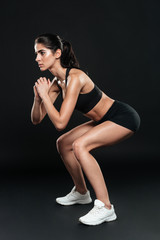 Fit girl working out doing squats with hands up