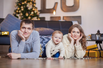 Happy family is lying on carpet tree and smiling