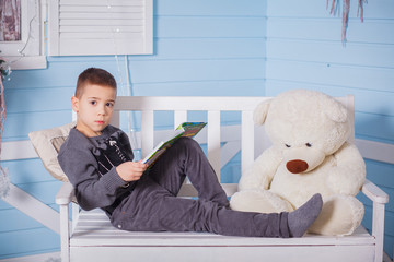 boy sitting near fireplace and Christmas tree with toy bear