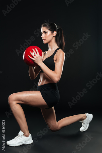 Concentrated sports woman doing squats and holding weight ball